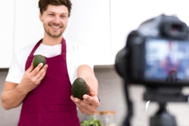 ハンサムな男性の自宅で料理ビデオを記録