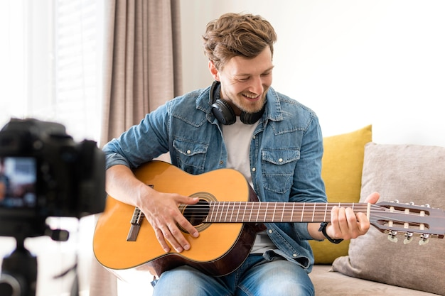 Handsome male recording guitar session at home