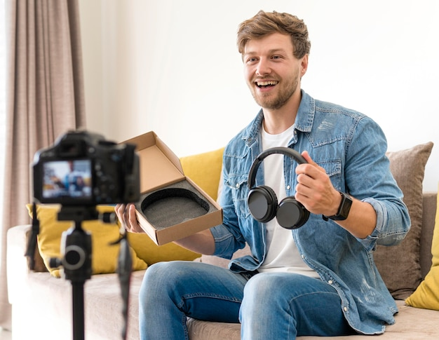 Handsome male recording unboxing video at home