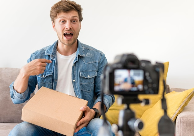 Handsome male recording unboxing video