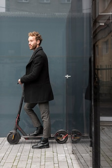 Handsome male riding an electric scooter