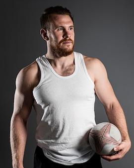 Giocatore di rugby maschio bello che tiene palla accanto all'anca