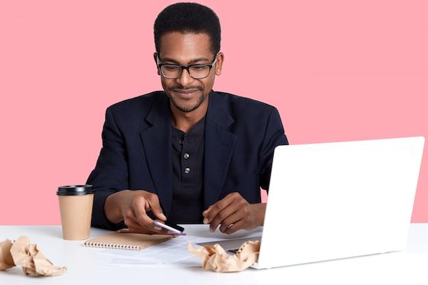 ハンサムな男性はラップトップと紙のしわくちゃのシャツで机に座っています。