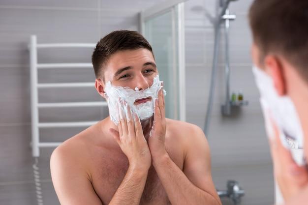 집에 있는 현대적인 타일 욕실에서 거울 앞에 서 있는 얼굴에 면도를 위한 잘생긴 남성 얼룩진 거품
