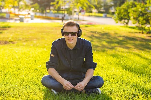 Красивый студент-мужчина сидит на зеленой траве и слушает музыку
