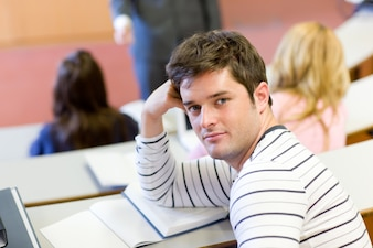 Handsome male student smiling at the camera during an university lesson