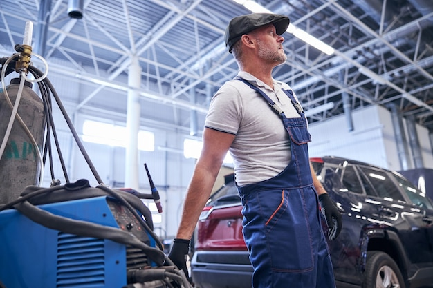 Handsome male technician in work overalls using professional automotive equipment at auto repair service station