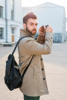 Handsome male traveler holding camera in hand looking at camera