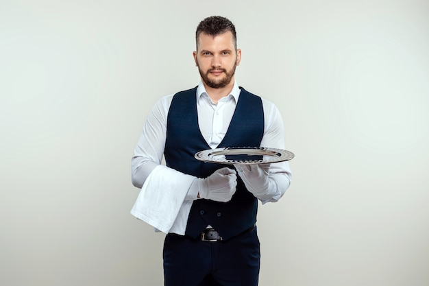 Handsome male waiter, in white shirt, holding a silver tray. the concept of serving staff serving customers in a restaurant.