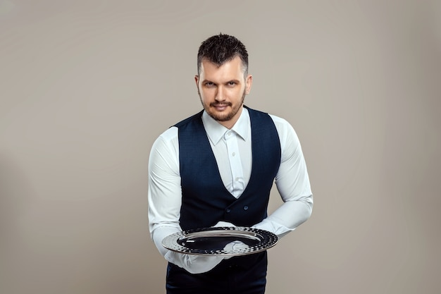 Handsome male waiter, white shirt, holds a silver tray, hand behind his back. concept of wait staff serving customers in a restaurant.