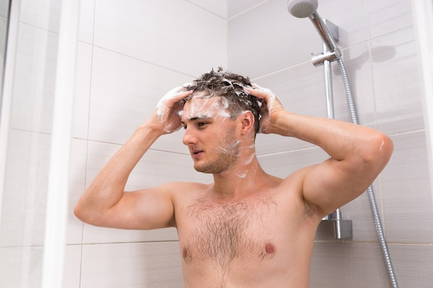 Handsome male washing his hair with both hands in shower cabin in the modern tiled bathroom