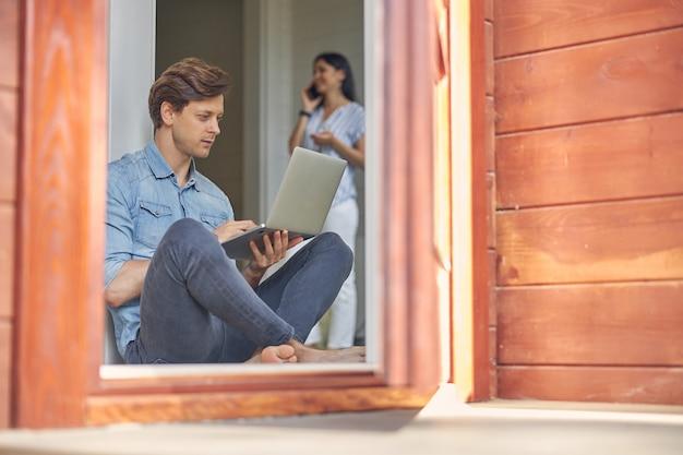 화면 현대 컴퓨터를 보면서 바닥에 앉아 캐주얼 옷을 입고 잘 생긴 남자