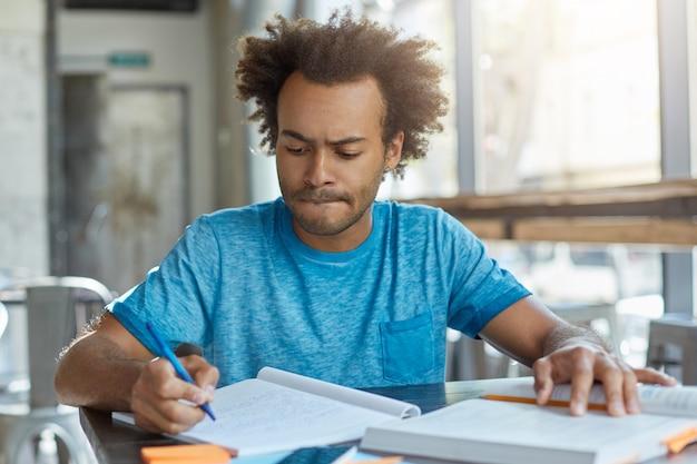 コーヒーショップに座っている彼の仕事に集中しようとしながら彼の下唇をかむ彼のコピー本で書いてアフリカの髪型を持つハンサムな男性。