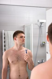 집에 있는 현대적인 타일 욕실에서 거울 앞에 서 있는 동안 면도기를 들고 나쁜 면도 후 얼굴에 상처가 있는 잘생긴 남성
