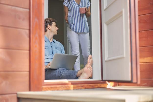 그의 여자 친구를 듣고 다리에 회색 노트북과 잘 생긴 남자