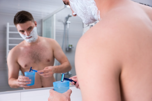 면도 거품을 뺨에 바르고 있는 잘생긴 남성은 집에 있는 현대적인 타일 욕실에서 거울 앞에 서 있는 물로 컵에 면도기를 씻습니다.