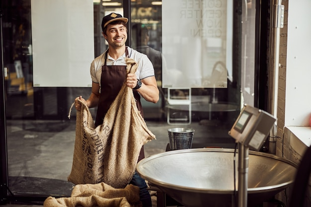 Handsome male worker in apron looking at camera and smiling while holding burlap sack with arabica coffee beans