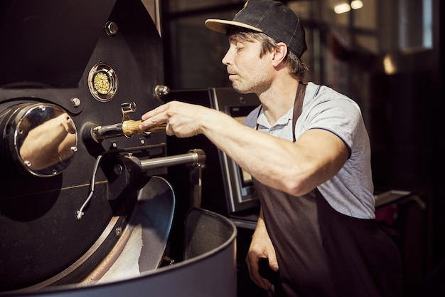 Handsome male worker in apron using industrial equipment for roasting coffee beans