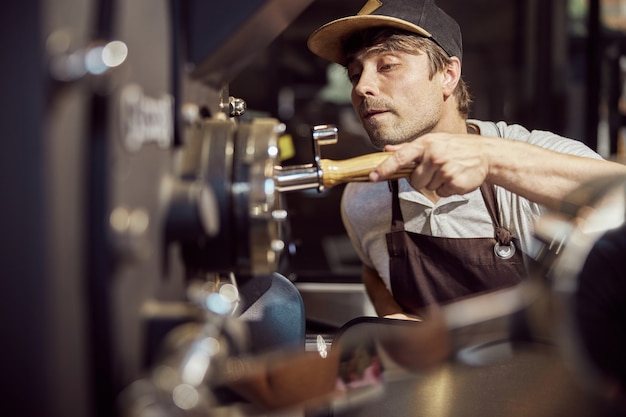 Handsome male worker in cap operating industrial equipment for roasting coffee beans