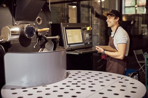 클립 보드를 들고 커피 로스팅 장비의 제어판 근처에 서있는 동안 웃고 앞치마에 잘 생긴 남성 노동자