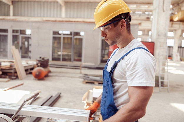 Handsome male worker using sawing machine in workshop