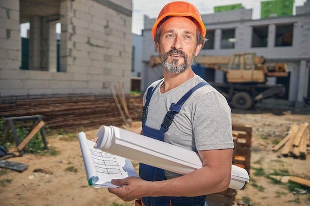 거리를 응시하는 그의 팔에서 종이 롤과 잘 생긴 남성 노동자