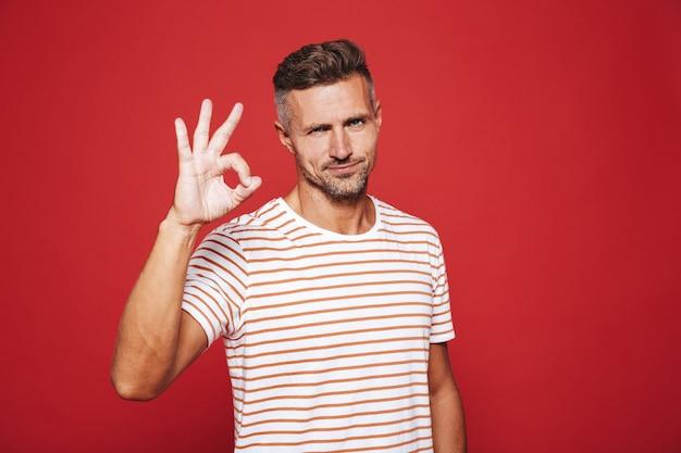 Красивый мужчина 30-х годов в полосатой футболке улыбается и показывает знак ок, изолированный на красном