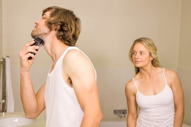 Handsome man about to shave with his girlfriend behind at home