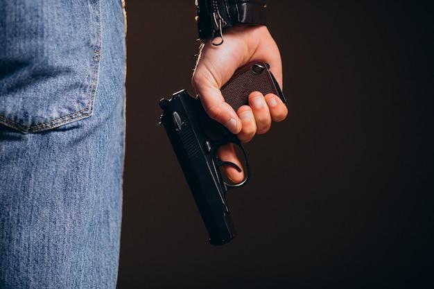 Красивый мужчина-актер позирует в студии с оружием