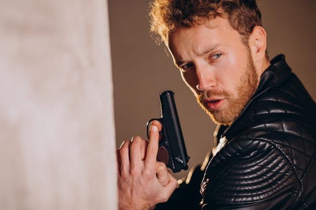 ハンサムな男俳優が武器を持ってスタジオでポーズをとる