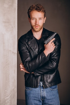 Handsome man actor posing in studio with weapon