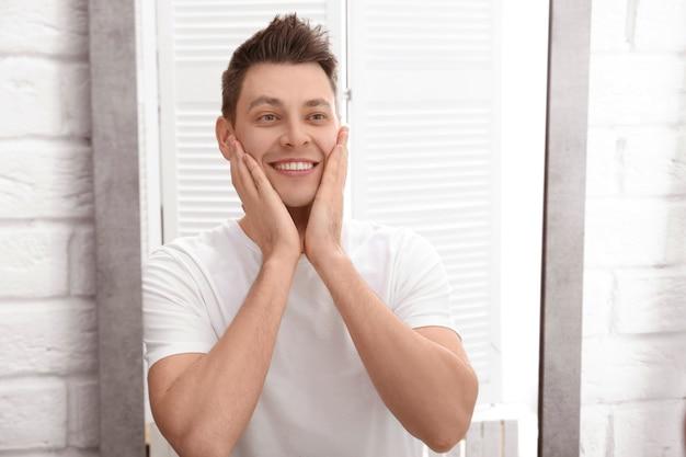 Красивый мужчина после бритья возле зеркала в ванной комнате
