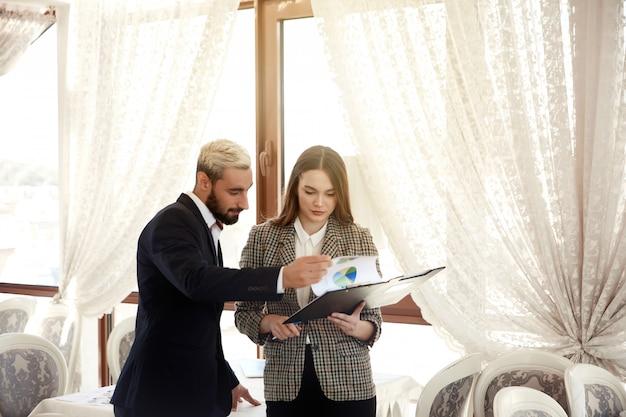 ハンサムな男とブルネットの女性は、図を見て、明るい部屋にいる