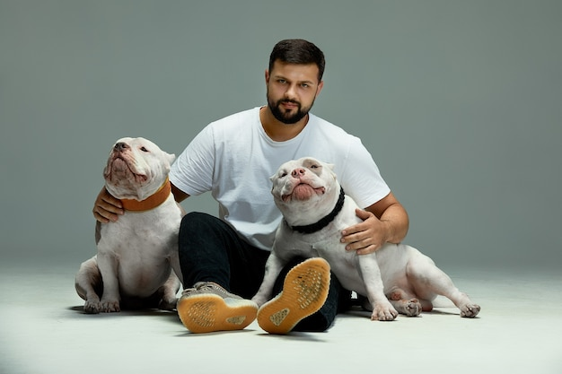 ハンサムな男と魅力的な犬のいじめっ子。クローズアップ、屋内。スタジオ写真、白い色。ケア、教育、服従訓練、ペットの飼育の概念