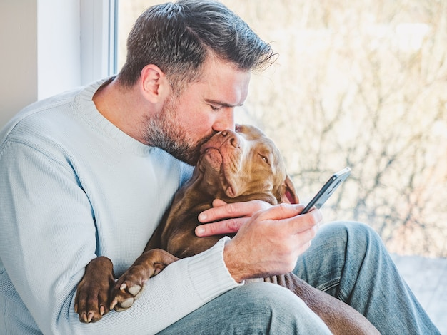 ハンサムな男と魅力的な子犬。クローズアップ、室内。スタジオ写真、白。ケア、教育、服従訓練、ペットの飼育のコンセプト