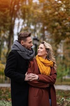Красивый мужчина и женщина обнялись сзади улыбаются, глядя друг на друга в осеннем парке
