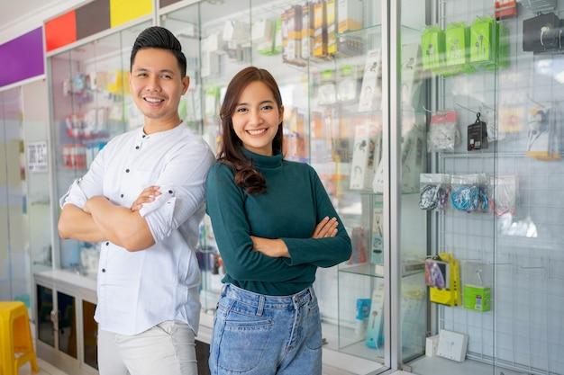 Красивый мужчина и красивая женщина, улыбаясь со скрещенными руками возле витрины с аксессуарами для сотовых телефонов