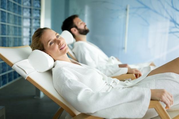 잘생긴 남자와 아름다운 여자는 목욕 가운을 입고 스파에서 시간을 보내고 휴식을 취합니다.