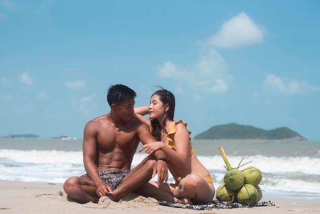 ハンサムな男と美しい女性の水着を着て、ビーチに座って、ロマンチックな気持ちで、モデルのポーズ
