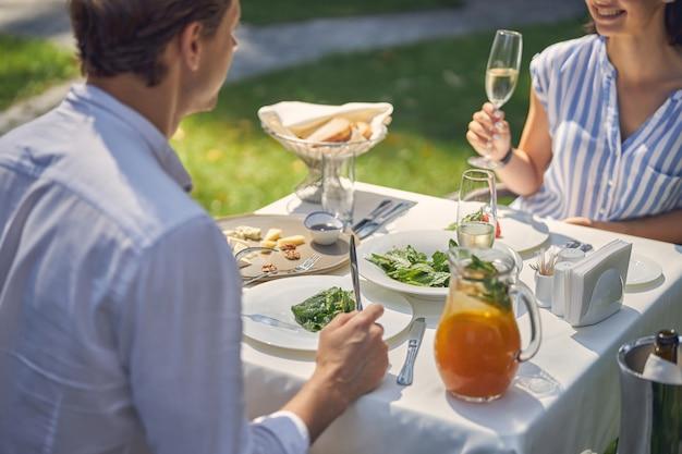 ハンサムな男性と魅力的な女性のサラダを食べて冷たいワインを飲む