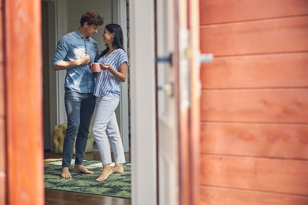 현대 집에서 서로를 찾고있는 동안 잘 생긴 남자와 차 한잔에 쉬고 매력적인 여자