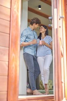 잘 생긴 남자와 그들의 호화로운 현대 집 문 근처에 서있는 매력적인 여자