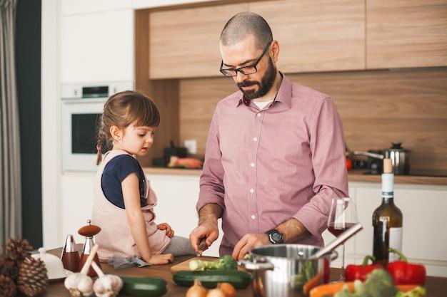 Красивый мужчина и его милая маленькая дочь вместе готовят овощное рагу на кухне. концепция здорового и вегетарианского питания.