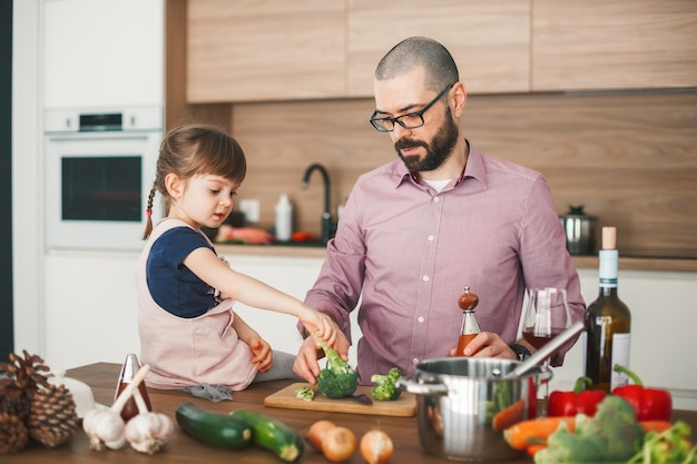 ハンサムな男と彼のかわいい小さな娘は、キッチンで一緒に野菜のシチューを調理しています。健康的でベジタリアン料理のコンセプト。