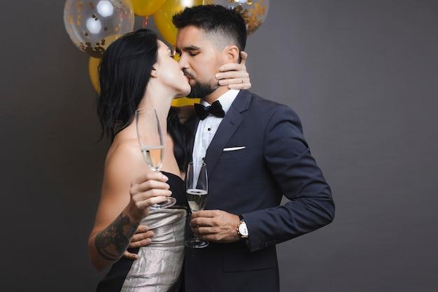 シャンパンのグラスを保持し、灰色の背景に風船の近くに立っている間情熱的にキスするエレガントな衣装でハンサムな男と素敵な女性