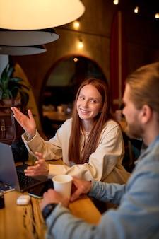 잘생긴 남자와 긍정적인 빨간 머리 여자는 커피를 마시는 동안 카페에서 비즈니스 프로젝트에 대해 논의합니다. 아늑한 카페테리아에서. 시작, 아이디어 및 두뇌 폭풍 개념입니다. 측면보기. 복사 공간