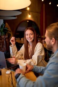 잘생긴 남자와 빨간 머리 여자는 커피를 마시는 동안 카페에서 비즈니스 프로젝트에 대해 논의합니다. 아늑한 카페테리아에서. 시작, 아이디어 및 두뇌 폭풍 개념입니다. 측면보기. 복사 공간
