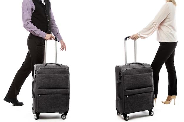 荷物を持って歩くハンサムな男と女。白い背景の上の若いカップルの側面図