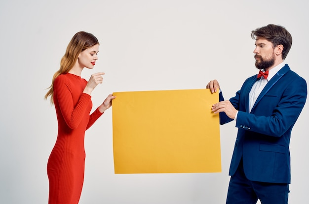 ハンサムな男性と女性の黄色のポピーパスツールポーズ広告