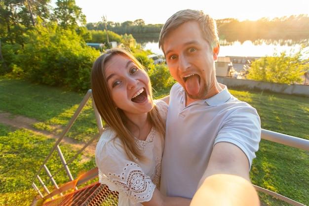 ハンサムな男性と若い女性が一緒に時間を過ごし、自分撮りを楽しんでいます。